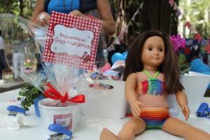 Mesa da oficina de bandeirinhas com a mascote da L'été, boneca Priscila.